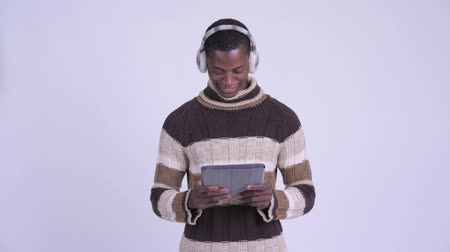 earmuff : Young happy African man thinking while using digital tablet ready for winter