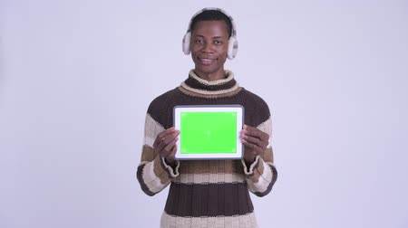 earmuff : Young happy African man thinking while showing digital tablet ready for winter