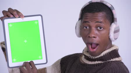 earmuff : Face of young happy African man showing digital tablet and looking surprised ready for winter