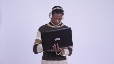 earmuff : Young happy African man using laptop ready for winter