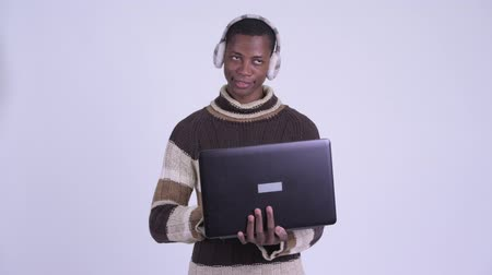earmuff : Young happy African man thinking while using laptop ready for winter
