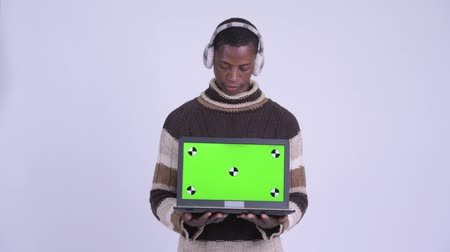 earmuff : Young happy African man thinking while showing laptop ready for winter