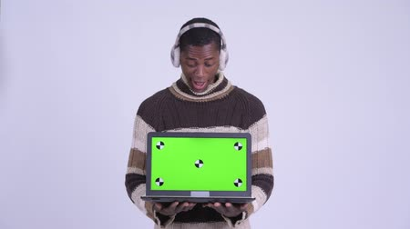 earmuff : Young happy African man showing laptop and looking surprised ready for winter Stock Footage