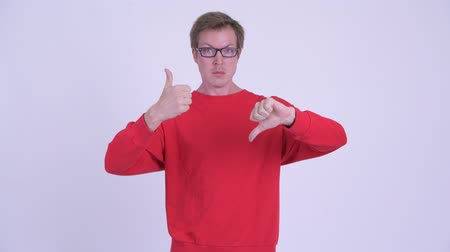 oy : Confused young man choosing between thumbs up and thumbs down Stok Video