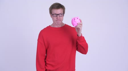 csalódott : Stressed young man holding piggy bank and giving thumbs down Stock mozgókép