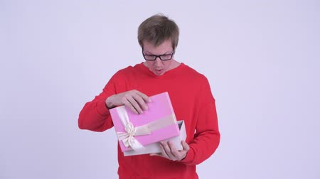 travessura : Young handsome man opening empty gift box and looking upset