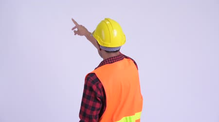 přímý : Rear view of young Hispanic man construction worker directing and pointing finger