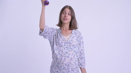 pesos : Happy young pregnant woman exercising with dumbbells Stock Footage
