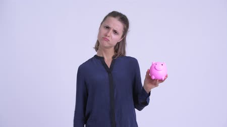 quebrado : Sad young businesswoman shaking piggy bank and looking upset