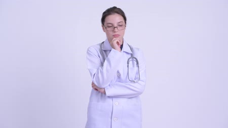 задумчивый : Serious young woman doctor thinking and looking down Стоковые видеозаписи