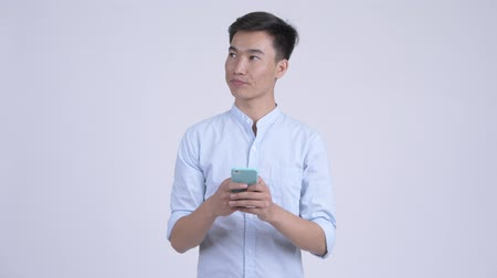 afghan : Young happy Asian businessman thinking while using phone Stock Footage