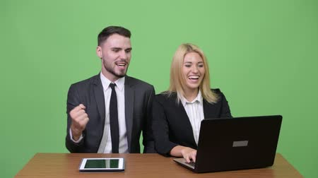 vysoká klíč : Young happy business couple using laptop together and getting good news