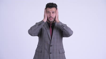 listens : Handsome bearded Persian businessman doing hear no evil concept Stock Footage