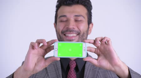 perzisch : Face of happy bearded Persian businessman thinking while showing phone Stockvideo