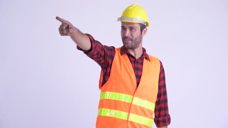 directing : Happy bearded Persian man construction worker directing and pointing finger Stock Footage