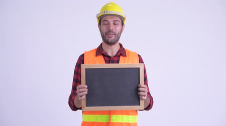 tablica : Happy bearded Persian man construction worker talking while holding blackboard