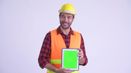 presentador : Happy bearded Persian man construction worker talking while showing digital tablet