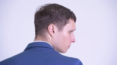 over the shoulder view : Rear view head shot of young handsome businessman looking back Stock Footage