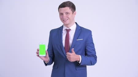 omologazione : Happy young handsome businessman showing phone and giving thumbs up Filmati Stock