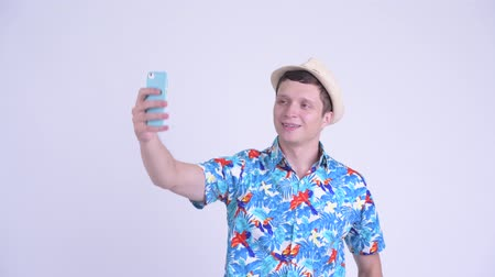 pensando : Happy young handsome tourist man taking selfie