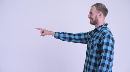 клетчатый : Profile view of happy bearded hipster man pointing finger