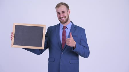 schválení : Happy bearded businessman holding blackboard and giving thumbs up Dostupné videozáznamy