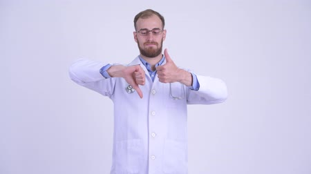 igen : Confused bearded man doctor choosing between thumbs up and thumbs down Stock mozgókép