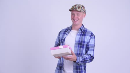 travessura : Young handsome hipster man opening empty gift box as prank