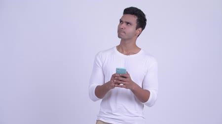 vlogging : Happy young Indian man thinking while using phone Stock Footage