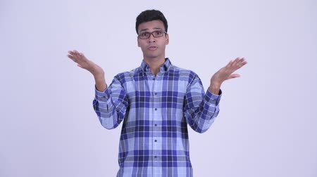 opinion : Confused young Indian hipster man giving thumbs up and thumbs down Stock Footage