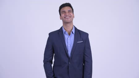 удовлетворения : Happy young handsome Indian businessman in suit smiling Стоковые видеозаписи