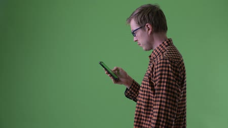 finnish : Profile view of happy young hipster man using phone
