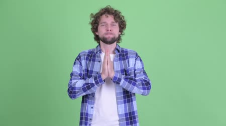 pleading : Young bearded hipster man looking desperate while praying Stock Footage