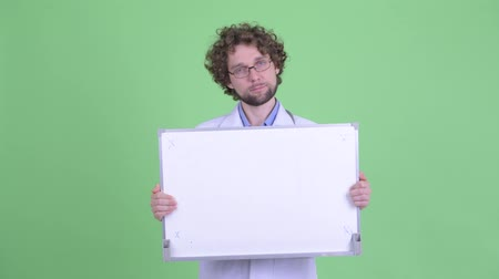 slecht nieuws : Stressed young bearded man doctor showing white board and looking frustrated