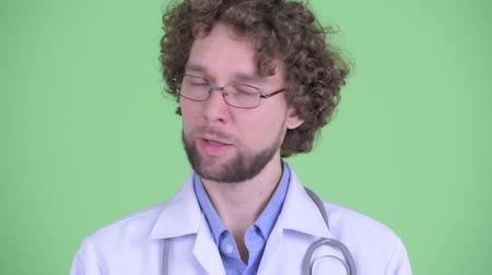 disagree : Face of serious young bearded man doctor nodding head no