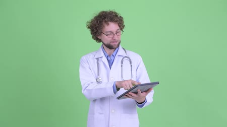 lab coat : Happy young bearded man doctor thinking while using digital tablet