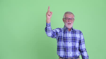 vay : Happy senior bearded hipster man pointing up and looking surprised Stok Video