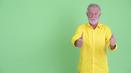human like : Happy senior bearded businessman showing something and giving thumbs up