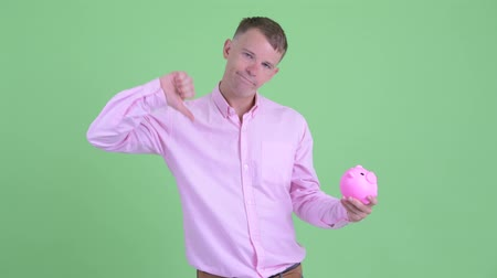 копилку : Stressed businessman holding piggy bank and giving thumbs down Стоковые видеозаписи