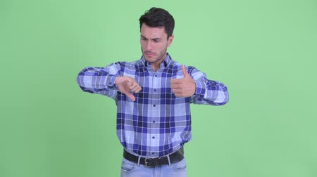 opinion : Confused young Hispanic man choosing between thumbs up and thumbs down