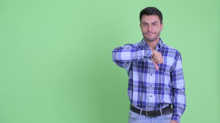 Stressed young Hispanic man showing something and giving thumbs down