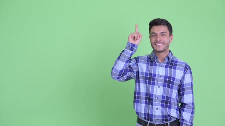 idéia genial : Happy young Hispanic man pointing up and giving thumbs up