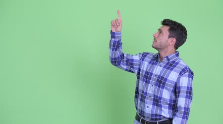 Stressed young Hispanic man pointing up and giving thumbs down Wideo