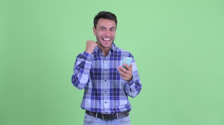 buenas noticias : Happy young Hispanic man using phone and getting good news