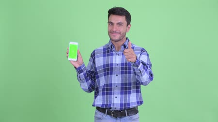 Happy young Hispanic man showing phone and giving thumbs up Wideo