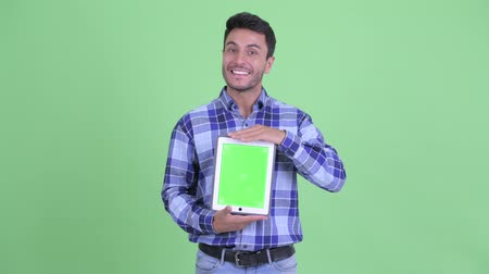 Happy young Hispanic man thinking while showing digital tablet