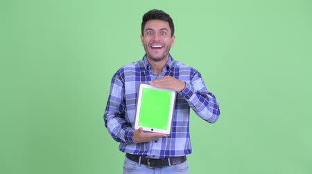 Happy young Hispanic man showing digital tablet and looking surprised Wideo