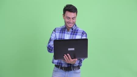 anız : Happy young Hispanic man thinking while using laptop Stok Video