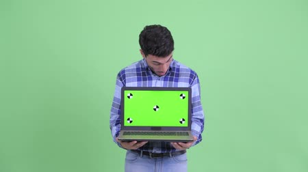 Happy young Hispanic man showing laptop and looking surprised