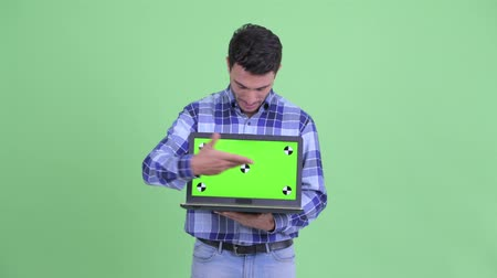 Young handsome Hispanic man talking while showing laptop